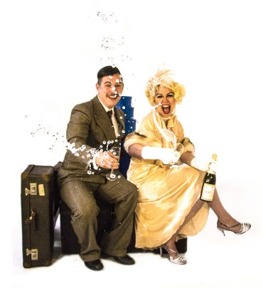 "Characters Oscar and Lily from ""On The Twentieth Century"" throw champagne towards the camera"